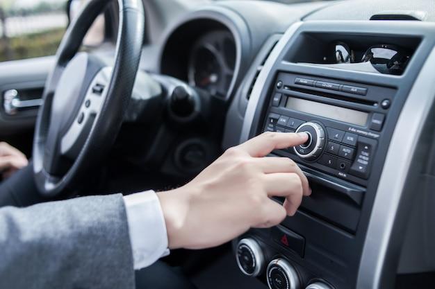 Человек с помощью аудиосистемы автомобиля аудио