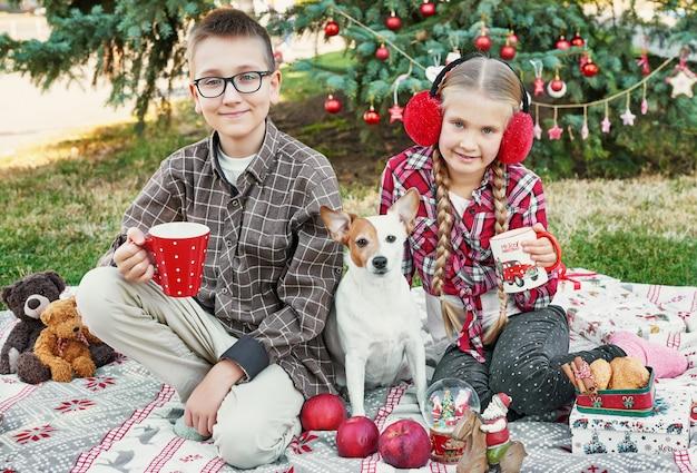 子供の男の子と女の子と犬のジャックラッセルテリアプレゼントとクリスマスツリーの近く、