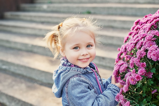 Ребенок девочка в парке возле клумбы хризантем осенью