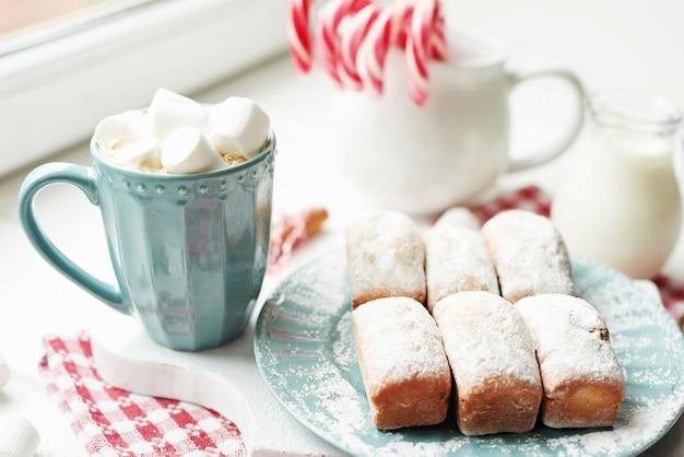 クリスマスのマフィン、ミルク、ココア、マシュマロ、窓辺の白い皿にキャンディロリポップ