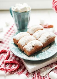 クリスマスのマフィン、牛乳、ココア、マシュマロ、窓辺のプレートにキャンディロリポップ