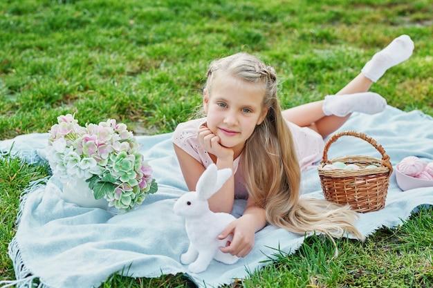 緑の芝生の公園でイースターのウサギと卵を持つ少女