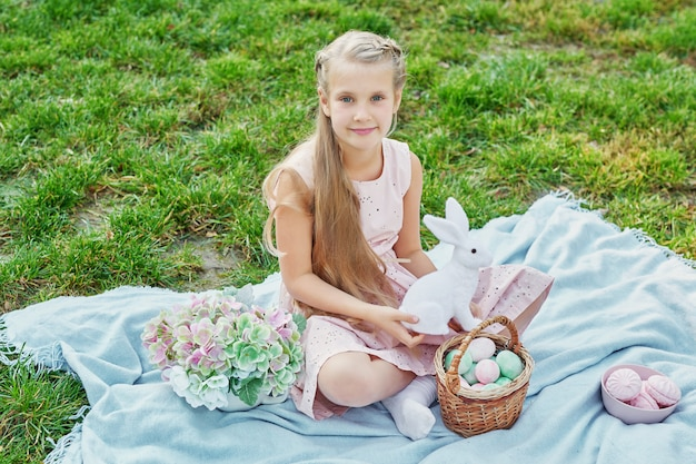 Девочка с кроликом и яйцами на пасху в парке на зеленой траве