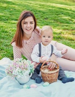 Семейная фотосессия мамы и маленького сына на пасху в парке, рядом с ними корзина с яйцами и пасхальный кролик