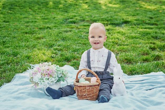 Мальчик с кроликом и яйца на пасху в парке на зеленой траве