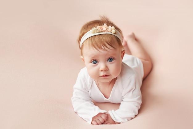 Девочка четырех месяцев лежит на светло-розовой стене