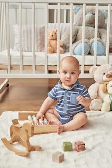Ребенок мальчик играет деревянные игрушки в детской комнате в светлых тонах, скандинавском стиле детская спальня