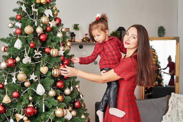 Семья возле елки. счастливая семья мать и ребенок возле елки в праздник. счастливого рождества и счастливых праздников! любящая семья с подарками в комнате.