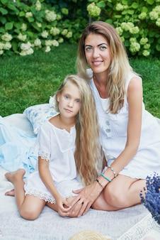 夏のピクニック休憩の庭で家族の母と娘