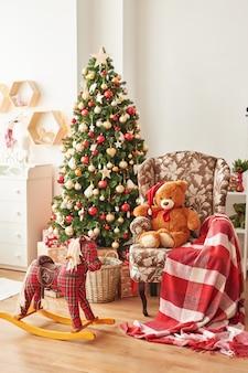 Рождественский интерьер детской спальнирождество в детской. лошадь-качалка и мягкая игрушка медведь на фоне елки.