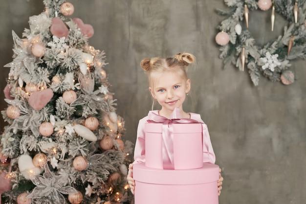 Милая маленькая девочка в розовом платье с подарками