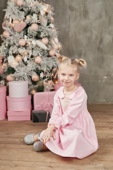 Милая маленькая девочка в розовом платье с елкой