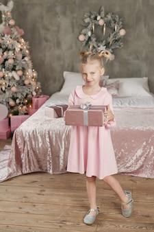 Милая маленькая девочка в розовом платье с подарком