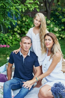 家族の父、母と娘のピクニック休憩の夏の庭で