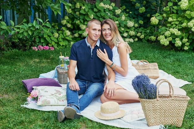夏の庭のピクニックの残りの家族の夫と妻
