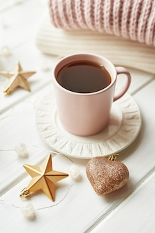 クリスマスの装飾、ボール、ウィンドウのウールチェック柄、家の快適さの概念、季節ごとの冬のお祝い。 。クリスマスピンクカップ