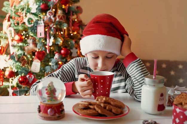 クリスマスツリーでお茶のクリスマス赤カップを持つ少年の笑顔。子供連れの家族は冬休みを祝います。自宅でクリスマスイブ。クリスマスキッチンの子少年。サンタ帽子の少年。