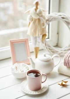 お茶セットと窓の近くのマシュマロと手作りの人形。居心地の良い冬の朝の朝食。クリスマスのコンセプトと気分。