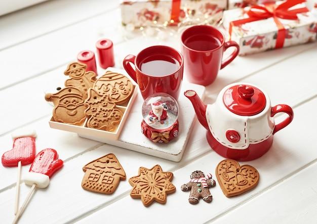 クリスマスクッキーと熱いお茶のマグカップ、クリスマスの時期。クリスマスのジンジャーブレッド、キャンディ、冷ややかな冬の日のウィンドウテーブルの上の木製のテーブルの上の赤いカップでコーヒー。居心地の良い休日。はがきテンプレート