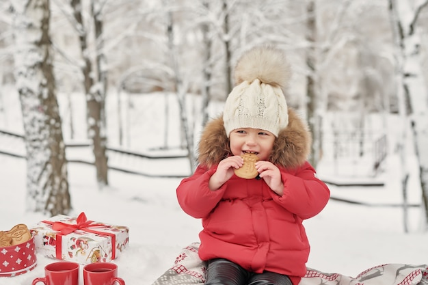 冬に幸せな子供の女の子は、お茶を飲みながら屋外を歩きます。冬のクリスマス休暇で遊ぶ小さな子供の笑顔の赤ちゃん。冬の公園でクリスマス家族。冬の森の少女。