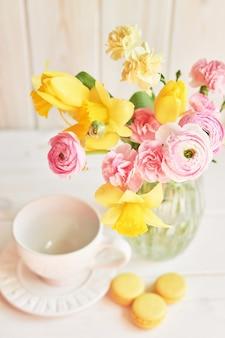 春の花の花束:チューリップ、カーネーション、ラナンキュリー、水仙の花瓶のテーブルの上。母の日挨拶