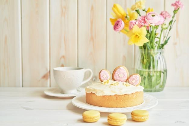 テーブル、マカロン、卵、花瓶の花の花束のイースターケーキ