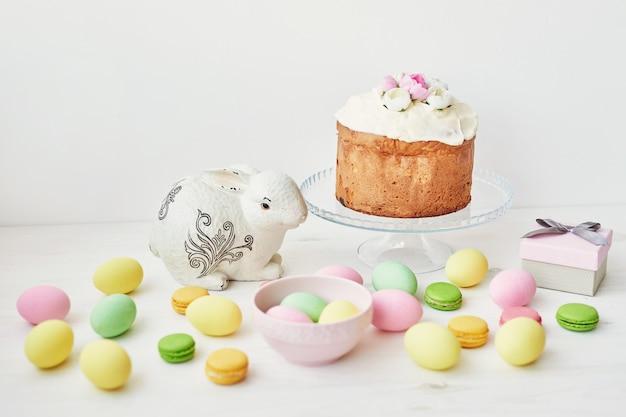 イースターの甘いパン、イースターケーキ、チューリップと白いウサギとマルチカラーの卵。コピースペースと休日朝食コンセプト。