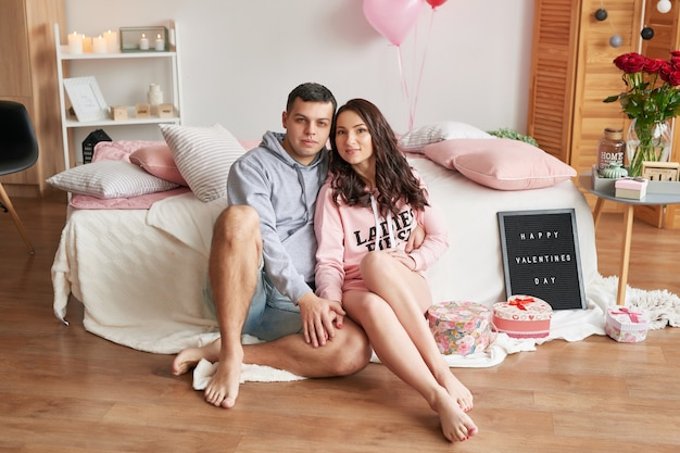 バレンタインの日を祝ってベッドに自宅で愛の若いカップル