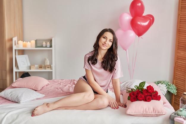 Молодая женщина на кровати в розовой пижаме с букетом красных роз