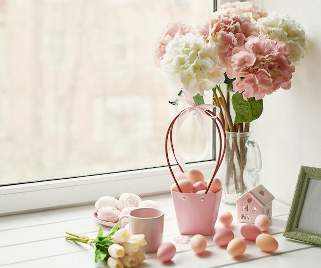 Пасхальная композиция с розовыми и белыми гортензиями в вазе, желтыми тюльпанами и розовыми яйцами