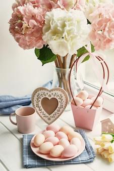 花瓶、黄色のチューリップ、ピンクの卵にピンクと白のアジサイのイースター組成