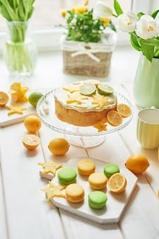 裸のケーキ、レモンとライム、甘いマカロンと花瓶の花