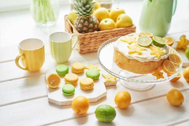 レモンとライム、フルーツ、甘いマカロンと白いチューリップの裸のケーキ