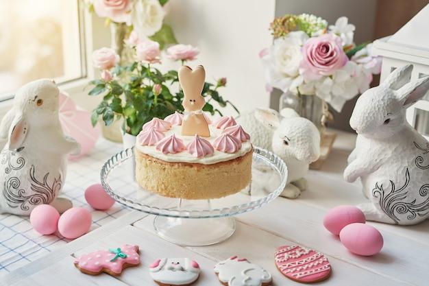 Пасхальная композиция со сладким пирогом с клубничной глазурью, керамическими кроликами, розовыми яйцами и розами