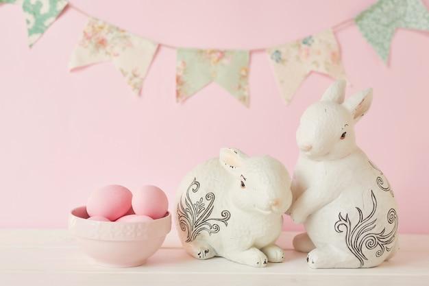 Пасхальные кролики с розовыми крашеными яйцами и гирляндой