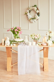 Христос воскрес! праздничные украшения. красивая праздничная сервировка стола пасха с кроликом, цветами и яйцами. весенняя цветовая тема, копия пространства. шаблон поздравительной открытки пасхи. кухонный интерьер.