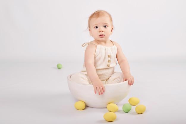 Милый малыш с расписными пасхальными яйцами