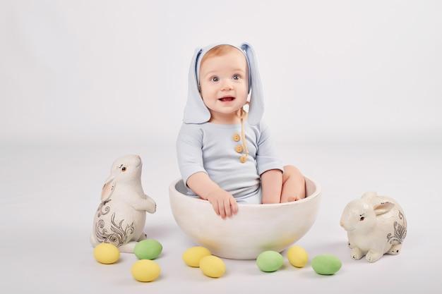 Милый малыш с расписными пасхальными яйцами и кроликами