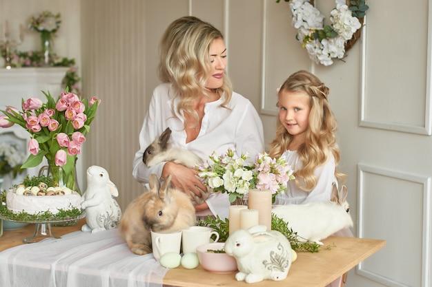 Милая девушка и мать, играя с кроликами