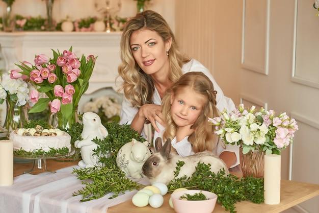 Милая девушка и мать, играя с кроликом