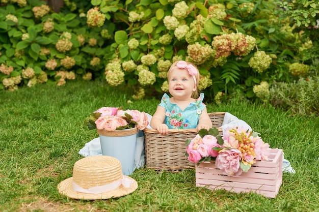 子供の保護の日、公園で女の赤ちゃんは夏のピクニックにバスケットに座っています。