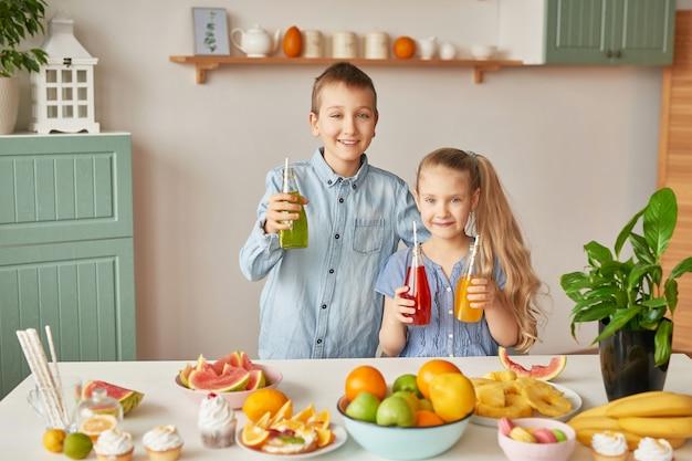 キッチンでジュースを飲む子どもたち