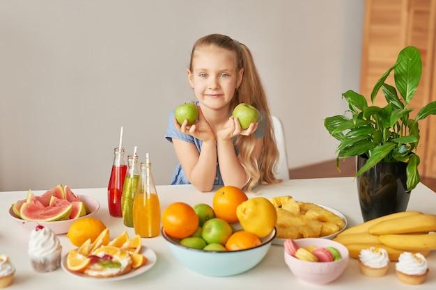 Девочка ест фрукты на столе, полном еды