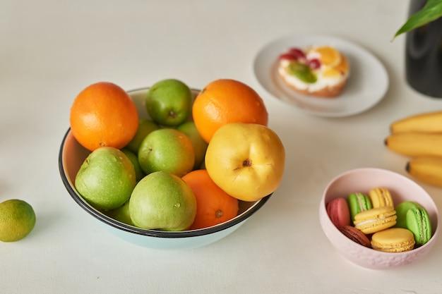 テーブルに熟した果物と甘いマカロンの山