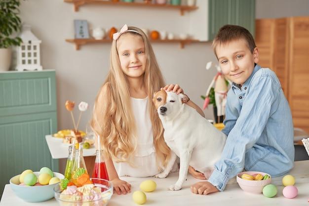 イースター装飾のテーブルで犬と遊ぶ子供たち