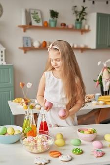 キッチンでイースターの卵を保持している女の子
