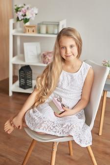 Обрадованная маленькая девочка с подарком