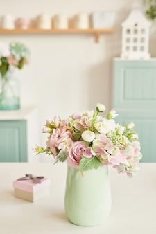 Светлая кухня в стиле прованс, на столе посуда и букет цветов в вазе