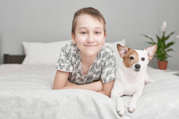 Двое друзей мальчик и собака вместе лежа на кровати. мальчик на кровати с собакой джек рассел терьер. концепция дружбы.