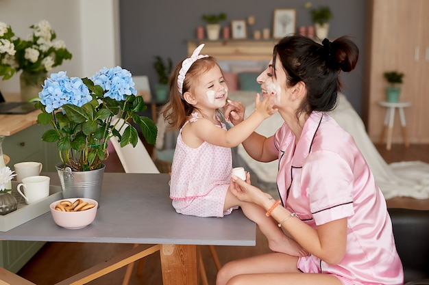 家族の母と朝の赤ん坊の娘は、キッチンで朝食をとります。